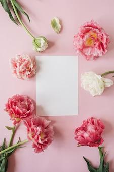 Blanco vel papier kaart in ronde frame van roze en witte pioenroos tulp bloemen op roze