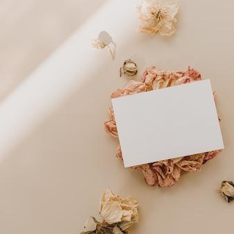 Blanco vel papier kaart met bloemknoppen met zonlicht schaduwen op beige