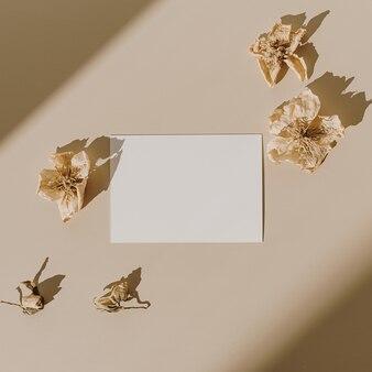 Blanco vel papier kaart met droge bloemknoppen met zonlicht schaduw op beige