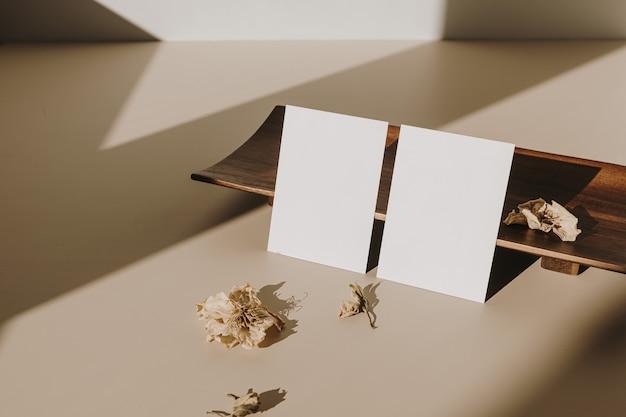 Blanco vel papier kaarten en houten dienblad, droge bloemen met zonlicht schaduwen op beige