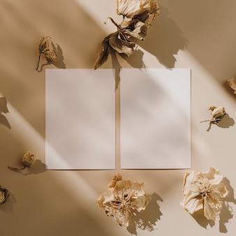 Blanco vel papier kaarten met droge bloemknoppen met zonlicht schaduw op beige
