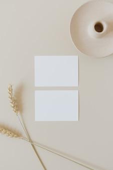 Blanco vel papier kaarten met kopie ruimte en tarwe rogge stengels op beige. minimale bedrijfsmerksjabloon. plat lag, bovenaanzicht