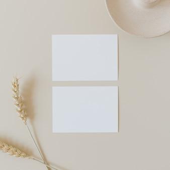 Blanco vel papier kaarten met tarwe rogge stengels op beige