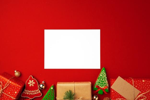 Blanco vel papier met kerstcadeau en peperkoek cookies op rode achtergrond