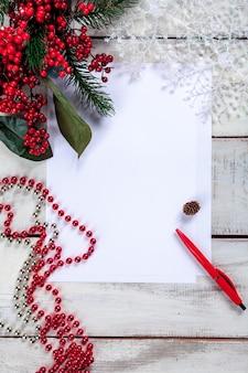 Blanco vel papier op de houten tafel met een pen en kerstversiering.