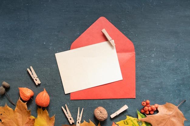 Blanco vel papier plat lag oranje herfstbladeren en envelop, physalis op een donkere achtergrond