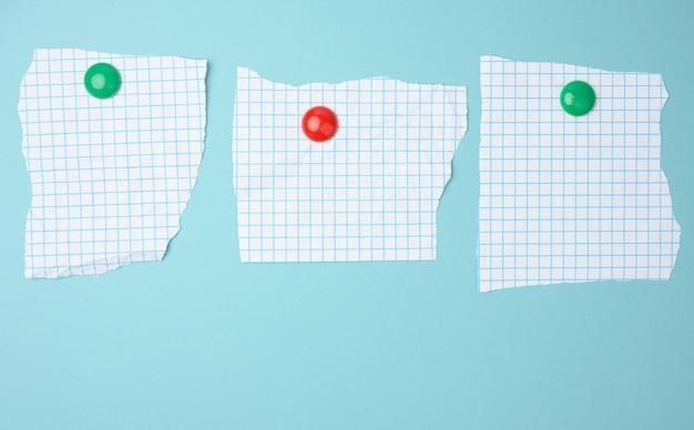 Blanco vellen papier in een kooi bevestigd aan een blauw magneetbord, ruimte voor een inscriptie