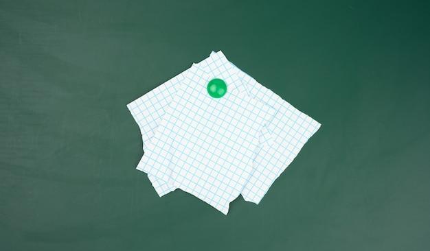 Blanco vellen papier in een kooi bevestigd aan een groen magneetbord, close-up