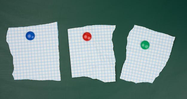 Blanco vellen papier in een kooi bevestigd aan een groen magneetbord, ruimte voor een inscriptie