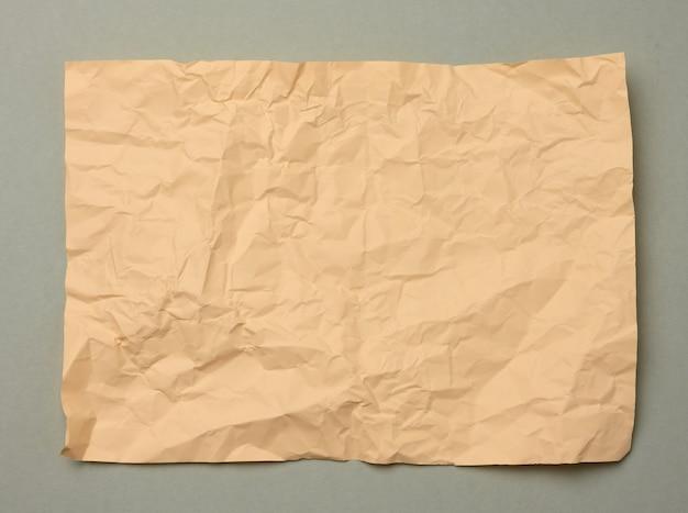 Blanco verfrommeld beige vel papier op een grijze achtergrond, kopieer ruimte. a4 formaat