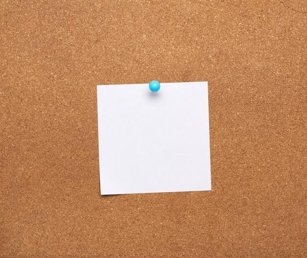 Blanco vierkant wit vel papier bevestigd met blauwe knop