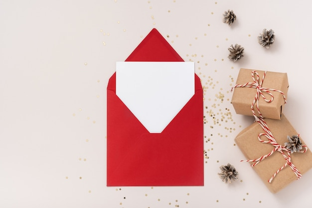 Blanco vierkante papieren mockup envelop rood, gouden sterren confetti, geschenkdozen op beige achtergrond.