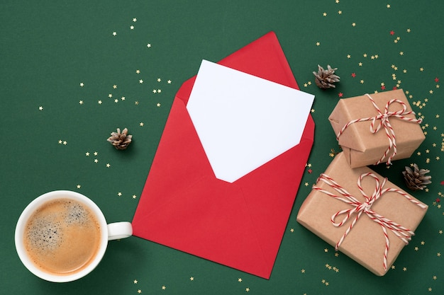 Blanco vierkante papieren mockup envelop rood, gouden sterren confetti, geschenkdozen op groene achtergrond.