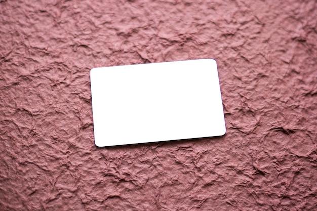 Blanco visitekaartje geïsoleerd op getextureerde magenta achtergrond