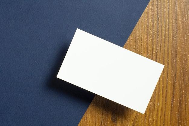 Blanco visitekaartjes de helft van elk liggen op blauw geweven papier en houten bureau