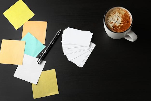 Blanco visitekaartjes met kopje koffie en pen op donkere tafel
