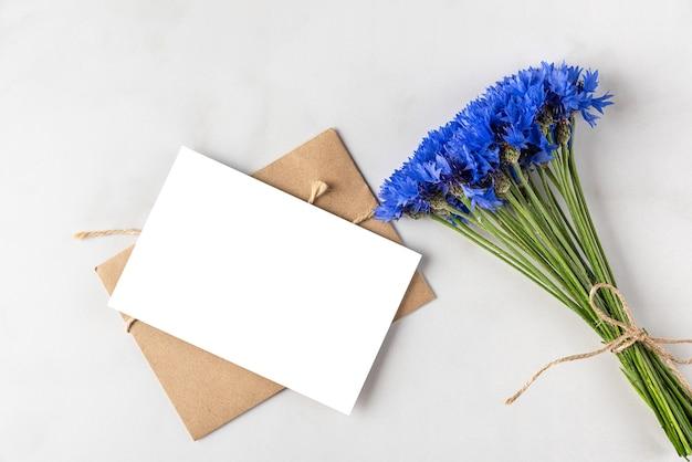 Blanco wenskaart met zomers blauw korenbloemenboeket op wit marmeren oppervlak