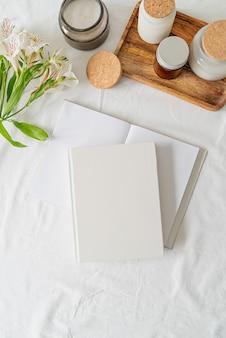 Blanco wit boek, koffie, glazen potten en bloemen op wit bed, plat gelegd