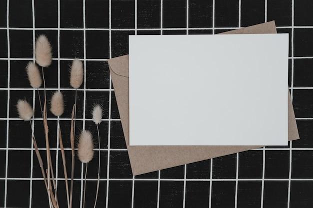 Blanco wit papier op bruine papieren envelop met droge bloem van de staart van het konijn en kartonnen doos op zwarte doek met wit rasterpatroon. mock-up van horizontale lege wenskaart. bovenaanzicht van craft-envelop.