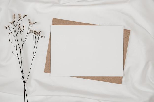 Blanco wit papier op bruine papieren envelop met droge bloem van limonium op witte doek