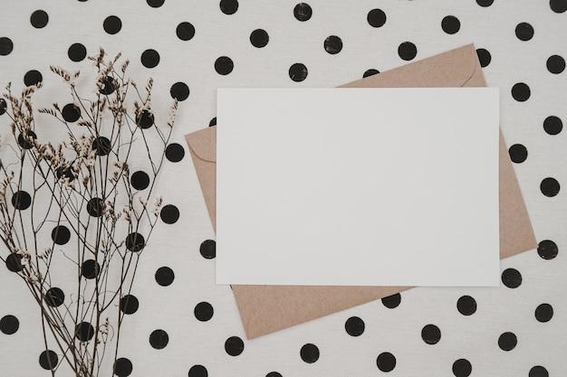 Blanco wit papier op bruine papieren envelop met droge limonium-bloem en kartonnen doos op witte doek met zwarte stippen. mock-up van horizontale lege wenskaart.
