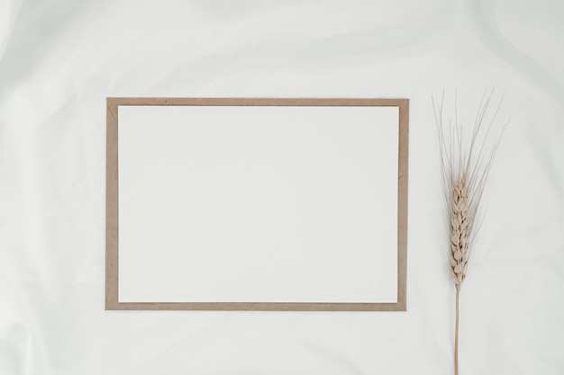 Blanco wit papier op bruine papieren envelop met gerst droge bloem op witte doek. horizontale lege wenskaart. bovenaanzicht van craft envelop op witte achtergrond.