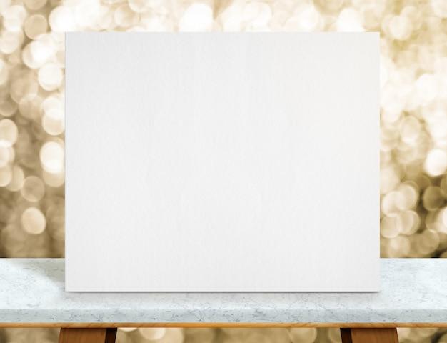 Blanco wit papier poster op marmeren tafelblad en sprankelend gouden bokeh licht