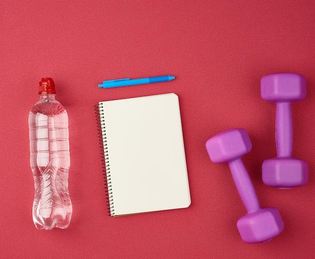 Blanco wit vel papier en pen, naast een halter, fles water