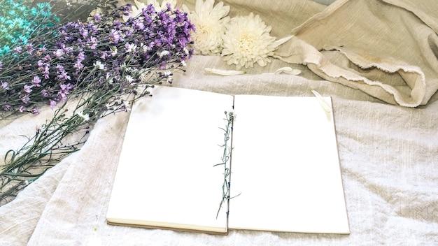 Blanco witboek notitieboekje en bloemdecoratie. wenskaart op een witte natuurlijk; linnen achtergrond. bovenaanzicht. ruimte kopiëren.