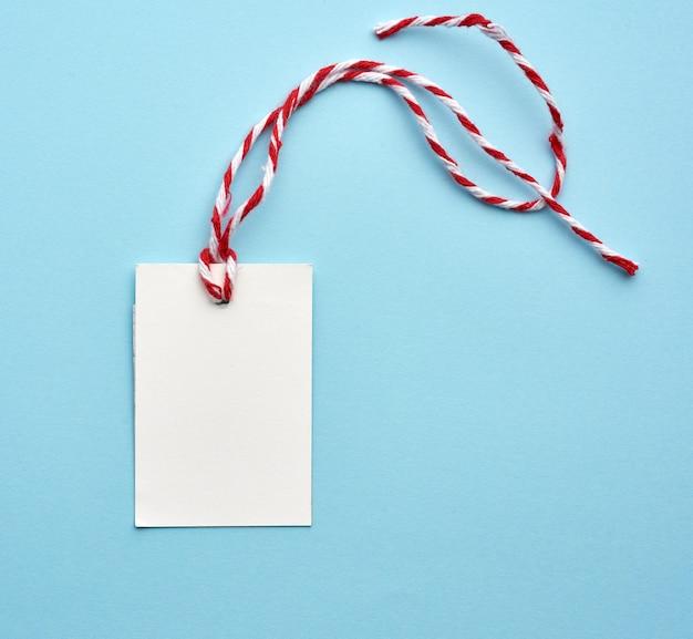 Blanco witboek tag met wit-rood touw op een blauwe achtergrond