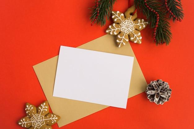 Blanco witboek voor tekst, envelop en kerst compositie op de rode achtergrond. bovenaanzicht. kopieer ruimte.