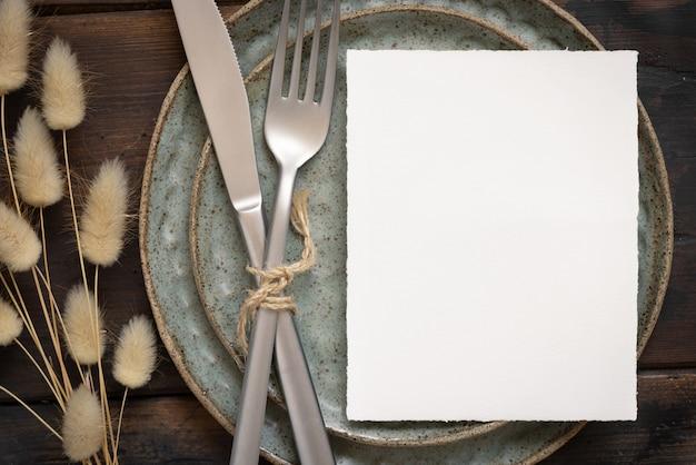 Blanco witte papieren kaart op bord met vork en mes op tafel met boheemse decoratie