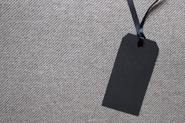 Blanco zwart papieren label op gestructureerde gestreepte stof