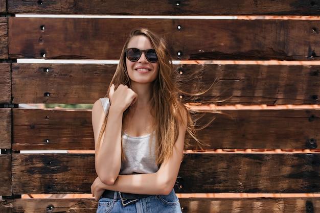 Blank meisje goede emoties uiten op houten muur. portret van prachtige bleke jonge vrouw draagt een donkere zonnebril.