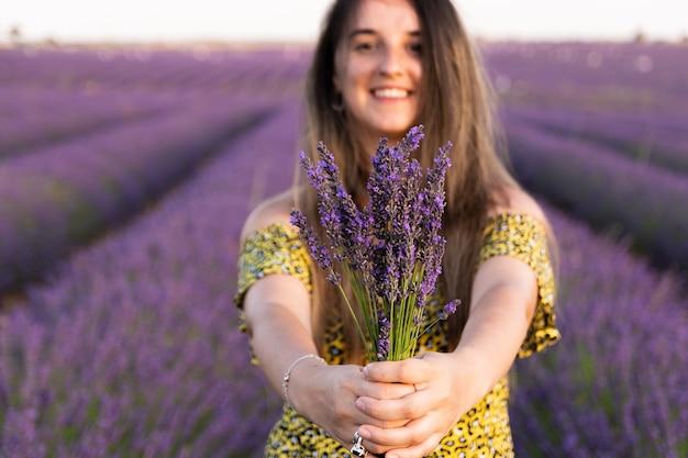 Blank meisje met een gele jurk, met haar haren naar beneden en een boeket lavendelbloemen in haar handen.
