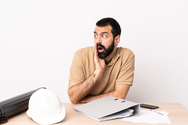 Blanke architect man met baard in een tafel iets met een verrassingsgebaar fluisteren terwijl hij naar de zijkant kijkt.