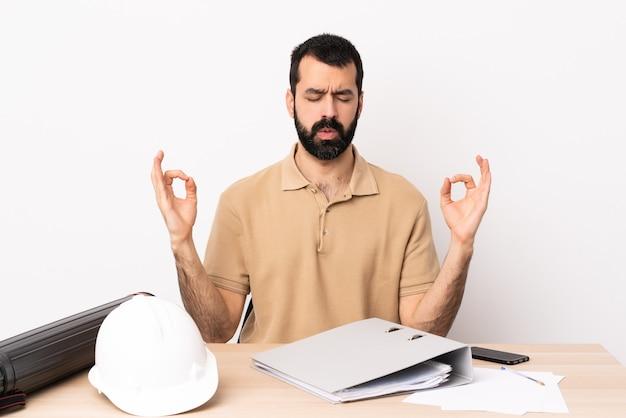 Blanke architect man met baard in een tafel in zen pose.