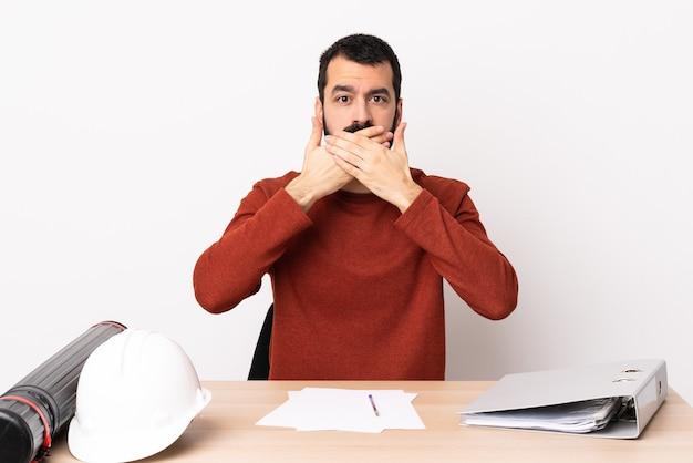Blanke architect man met baard in een tafel kegelvormige mond met handen.