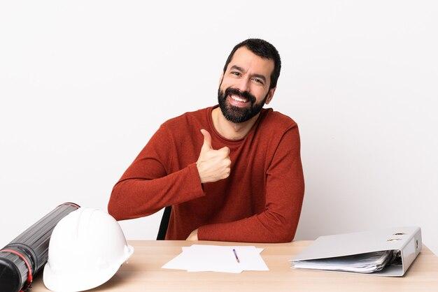 Blanke architect man met baard in een tafel met een duim omhoog gebaar.