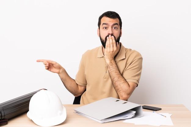 Blanke architect man met baard in een tafel met een verbaasde uitdrukking terwijl hij naar de zijkant wijst.