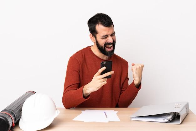 Blanke architect man met baard in een tafel met telefoon in overwinningspositie.