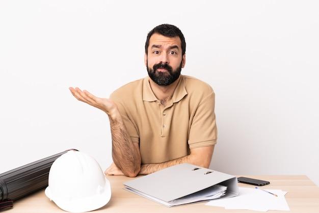 Blanke architect man met baard in een tafel met twijfels.