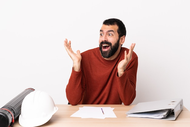 Blanke architect man met baard in een tafel met verrassende gezichtsuitdrukking.