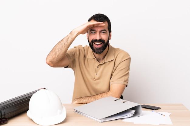 Blanke architect man met baard in een tafel op zoek ver weg met de hand om iets te kijken.