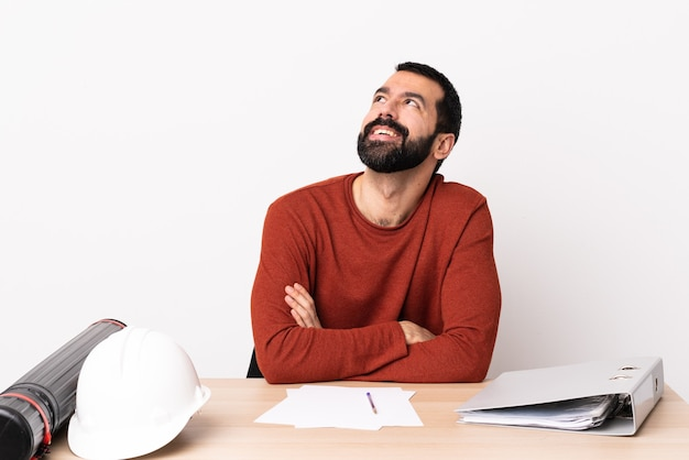 Blanke architect man met baard in een tafel opzoeken terwijl lachend.