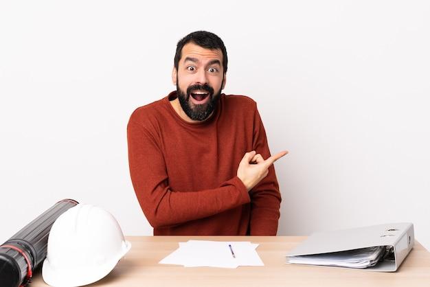 Blanke architect man met baard in een tafel verrast en wijzende kant.