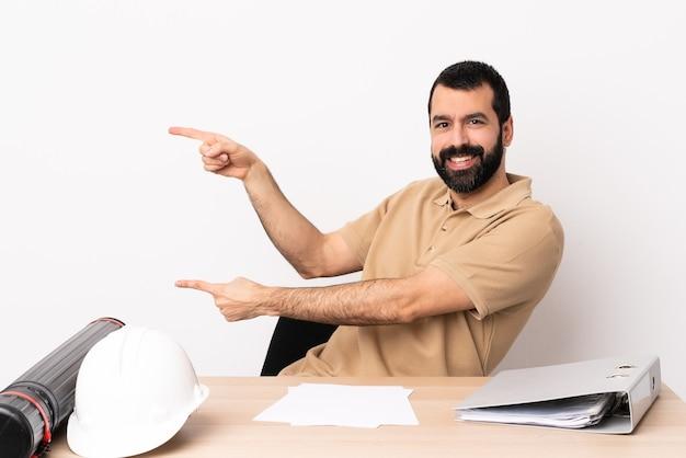 Blanke architect man met baard in een tafel wijzende vinger naar de zijkant en presenteert een product.