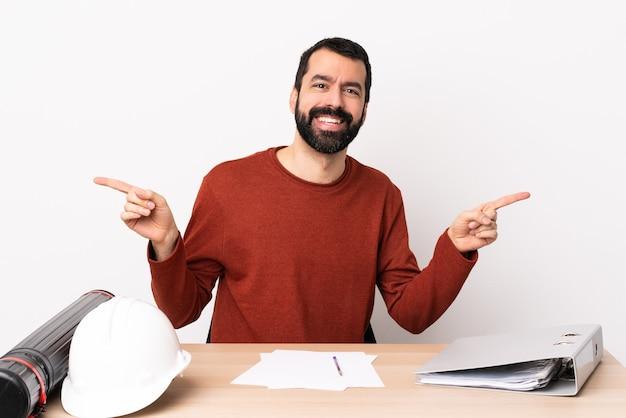 Blanke architect man met baard in een tafel wijzende vinger naar de zijtakken en gelukkig.