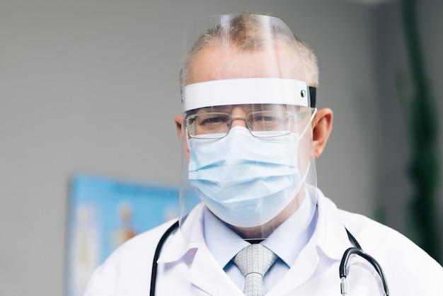 Blanke arts met een bril draagt een transparant beschermend gezichtsmasker en een overall in een ziekenhuiskamer