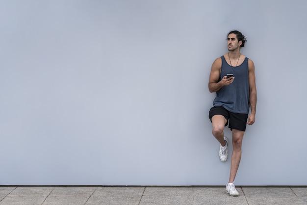 Blanke atleet man met smartphone op een trainingspauze
